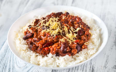 Chili con carne served with white long-grained rice and grated cheese