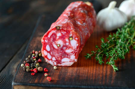 Italian salami with fresh thyme on the wooden board