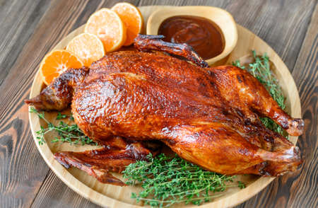 Baked duck with fresh thyme and oranges on wooden tray