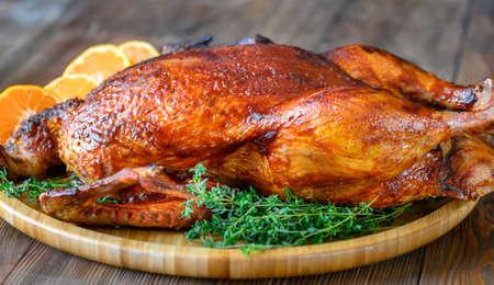 Gebackene Ente mit frischem Thymian und Orangen auf Holztablett