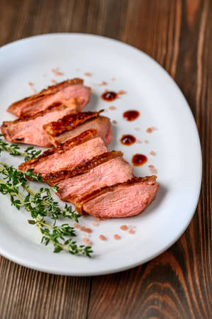 Slices of duck breast on the white plate