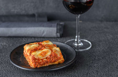 Dish of lasagne with glass of wine