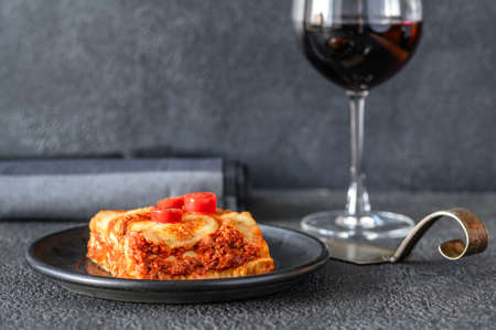 Dish of lasagne with glass of wine Banco de Imagens - 138543065