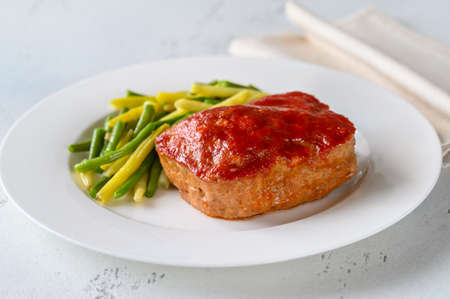 Meatloaf topped with tomato sauce with green beans