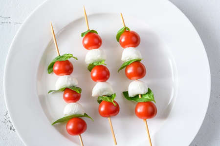 Caprese Salad skewers on white plate: top view