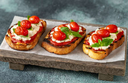 Italian Bruschettas with mozzarella, riccotta, baked tomatoes and basil