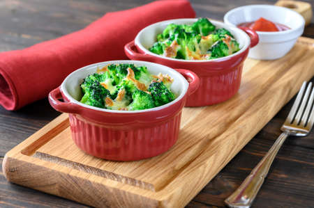 Two pots with baked broccoli and cheese on wooden board