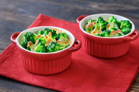 Two pots with baked broccoli and cheese