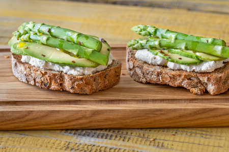 Avocado asparagus toasts with ricotta on cutting board