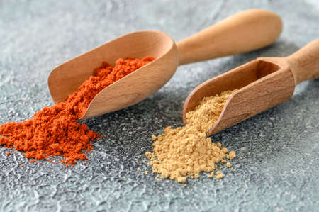 Red paprika and ginger powder in wooden scoop close-up