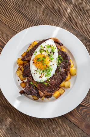 Beefsteak with fried egg and potato flat lay Foto de archivo