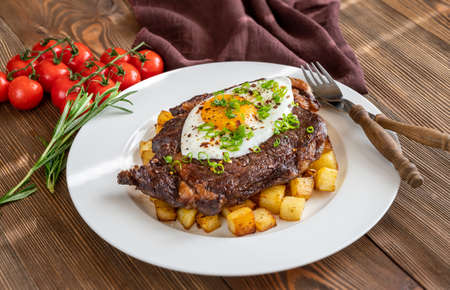 Beefsteak with fried egg and potato close up