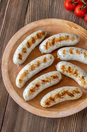 Grilled sausages with bunch of cherry tomatoes on plate Standard-Bild