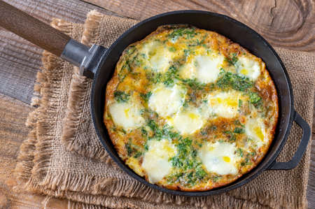 Frittata with ground meat and mozzarella in a frying pan