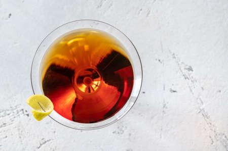 Glass of Martinez cocktail garnished with lemon zest