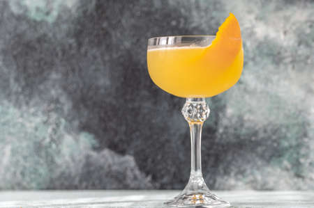 Glass of Bee's Knees cocktail garnished with orange zest