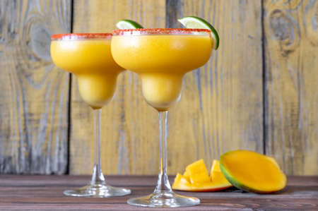 Glasses of Frozen Mango Margarita cocktails garnished with paprika salt rim