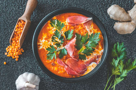 Bowl of lentil tomato and coconut soup with sliced prosciutto