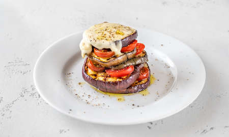 Sliced eggplant with cherry tomatoes and melted mozzarella