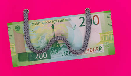 Going to the store for shopping, the handle of a shopping bag lies on a ruble banknote