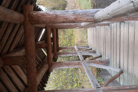 Wooden footbridge with a roof and railings across the river, autumn