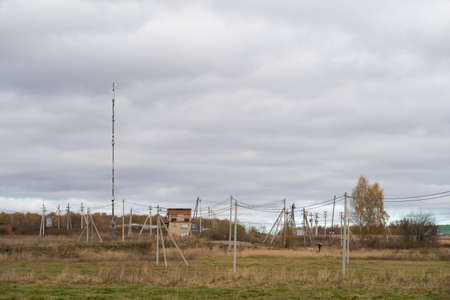 Poles of rural power lines with a transformer box and a mast with mobile antennas, autumn colors, cloudy
