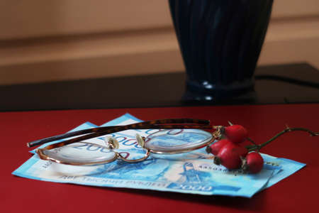 Banknotes, glasses and rose hips on the cover of a laptop against the background of a table lamp and a log wall, dacha, remote