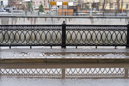 Metal grates of the fence on the embankment of the Vodootvodny Canal in Moscow, autumn, rainy day Stock Photo