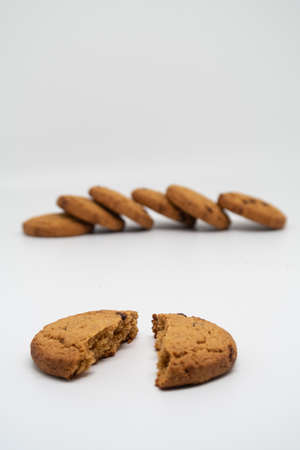 Broken oatmeal cookies in two halves with a stack of cookies in the background, bakery products Reklamní fotografie