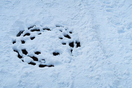 Metal manhole cover with holes and melted snow on the carriageway, winter snow background