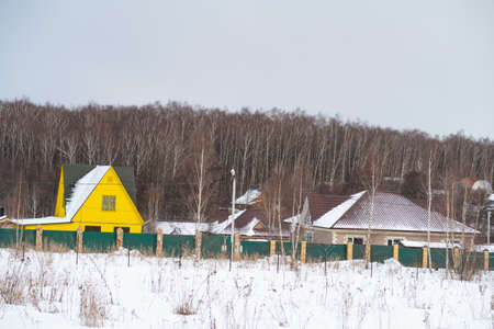 Snow covered field and country houses on the background of a birch grove, background Banque d'images