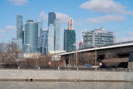 Moscow river embankment and automobile bridge against the background of urban planning, 2021