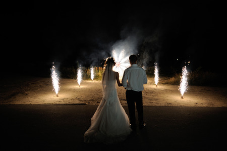 Bride and groom on the background of wedding fireworks.