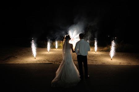 결혼식 불꽃 놀이의 배경에 신부와 신랑입니다.