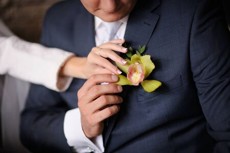 corrects: Bride corrects groom boutonniere.