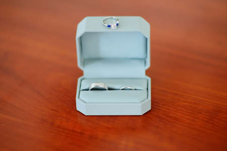 platinum: Pair of platinum wedding rings in the box and ring with diamond on the box.