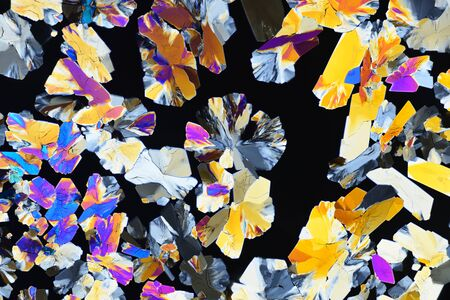 Photo through a microscope of crystals grown from a solution of citric acid in alcohol. Polarized light technology. Abstract art wallpaper. Background for design. Reklamní fotografie