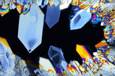Photo through a microscope of crystals grown from a melt of sulfamic acid. Polarized light technology. Abstract art wallpaper. Background for design.