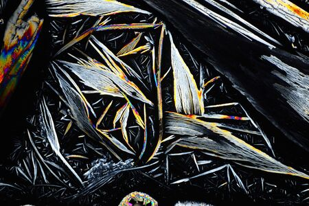 Photo through a microscope of crystals grown from a solution of benzoic acid in alcohol. Polarized light technology. Abstract art wallpaper. Background for design.