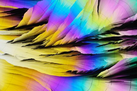 Photo through a microscope of crystals growing from the melt of sulfur. Polarized light technology. Abstract art wallpaper. Background for design.