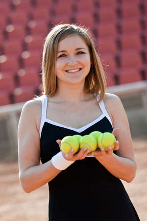 Girl holding a tennis balls while standing on a tennis court for lessons. photo