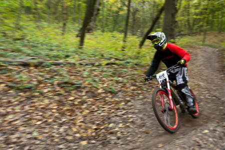 UKRAINE, KIEV - OCTOBER 16: Unknown professional biker with blurred background making his road, at the professional bicycle downhill final competition Kyiv Cup, on October 16, 2011 at Ukraine, Kiev. Stock Photo - 11215294