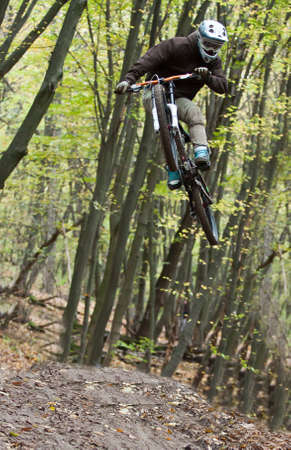UKRAINE, KIEV - OCTOBER 16: Unknown professional biker with blurred background making his road, at the professional bicycle downhill final competition Kyiv Cup, on October 16, 2011 at Ukraine, Kiev.