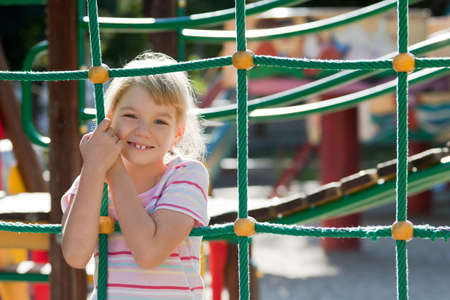 Little girl on the playground having fun at summer time. Stock Photo