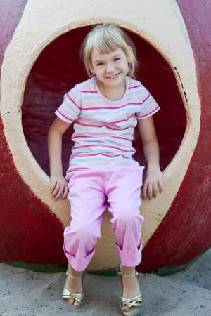 Little girl on the playground having fun at summer time. photo