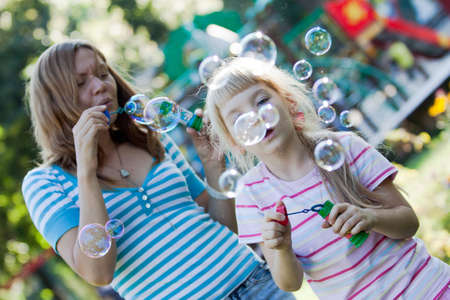 Two sisters making water bubbles at summer time.