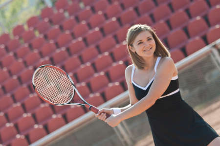 Girl playing with a tennis racquet on a tennis court for lessons. Stock Photo - 11723208