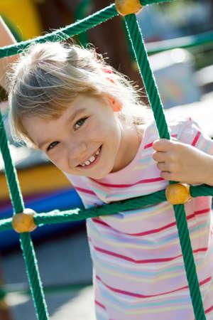 convivencia escolar: Ni�a en el patio de recreo que se divierte en el horario de verano.