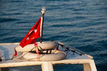 The red Turkish flag with star and moon, on the sea background. photo