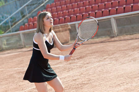 Girl playing with a tennis racquet on a tennis court for lessons. photo
